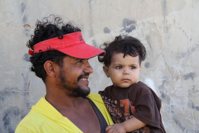 A Palestinian father holds his son in Gaza. Liz O'Neil/CRS