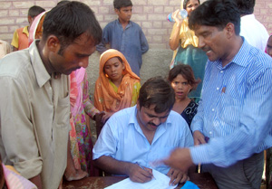 Ameen Babar monitoring the issuance of slips to recipients. Credits: Caritas Pakistan