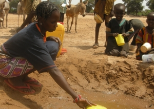 "Mary Namuroi scoops water from a sand dam. ""We are forced to share our water supply with animals,"" she says. Credits: Laura Donkin/CAFOD"
