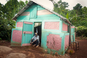 A man in front of his house, a part of local reconstruction and rehabilitation of traditional houses project. Credits: Secours Catholique