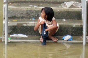 A girl washes clothes in flood water. CRS Philippines is procuring water containers and hygiene kits in other parts of the country for distribution to flood victims. Credits: NASSA-Caritas Philippines