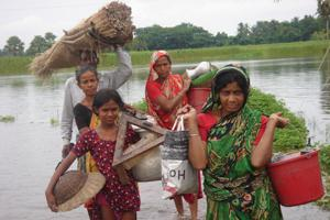 In a flooded area in Bangladesh, people salvage their household items and carry them in buckets. Credits: Caritas Bangladesh