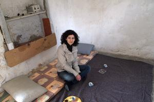 Caritas Lebanon's Rita Rhayem sits in a room occupied by three Syrian families in Bekaa Valley, Lebanon. Caritas will support Syrian refugees in Bekaa with blankets, heaters, personal hygiene equipment. Hundreds of families have fled Syria to Lebanon since fighting broke out in Syria in March 2011. Credits: Patrick Nicholson/Caritas