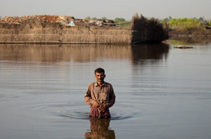 A man wades through floodwaters to reach his family's makeshift camp in a village in Sindh province, Pakistan. Credits: Asaid Zaidi / Caritas