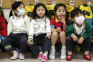 Kindergarten students wear masks while attending a lesson in Hong Kong April 30, 2009. The World Health Organization said on Wednesday the world is at the brink of a pandemic, raising its threat level as the swine flu virus spread and killed the first person outside of Mexico, a toddler in Texas. Credits: REUTERS/Tyrone Siu (CHINA EDUCATION HEALTH)