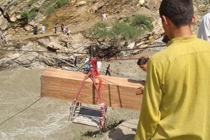A dead boy's coffin is transported over a washed-out area via a rope trolley in northern Pakistan, where massive flooding has killed over 1000 people and destroyed thousands of homes. Catholic Relief Services is helping flood survivors with items such as water purification tablets, soap, buckets, and cookware. CRS is also planning to distribute emergency shelter kits. Credits: Catholic Relief Services Staff, Bersham