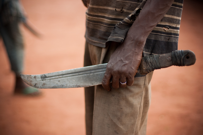 A man holds a machete (aka Balaka in Songo) on November 8, 2013 in the outskirts of Bangui. Chaos followed the ouster of Francois Bozize earlier this year, opposing the anti-Balaka and the ex-Seleka rebels and reports of summary executions, looting and abuses against civilians have prompted international concern that the Central African Republic could become another Somali-style failed state. Credit: Matthieu Alexandre/Caritas