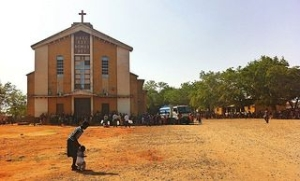 People cling to the shade as they receive aid from Caritas in Juba in the early days of the conflict. Credit: Caritas