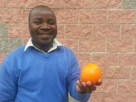 Carsterns Mulume, National Director of CADECOM, holds an orange while at a 'Food for All' meeting in Rome, Italy. Credit Laura Sheahen/Caritas