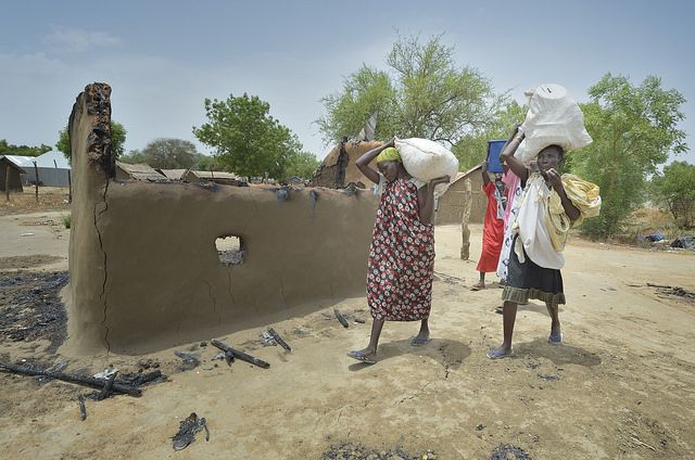 Displaced women walk past burned homes as they return to Bor, a city in South Sudan's Jonglei State that has been the scene of fierce fighting in recent months. Photo by Paul Jeffrey for Caritas