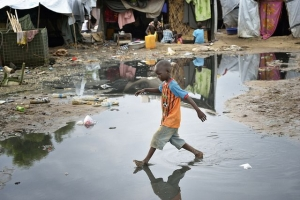 A boy navigates a flooded portion of a camp for internally displaced families located inside a United Nations base in Juba, South Sudan. Photo by Paul Jeffrey for Caritas