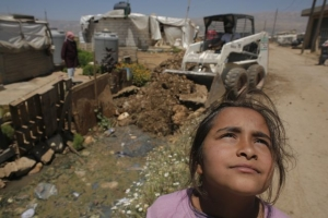 A Syrian refugee girl looking on as a tractor pours sand into a septic drain on June 17, 2014 in Zahle. Matthieu ALEXANDRE for CARITAS INTERNATIONALIS