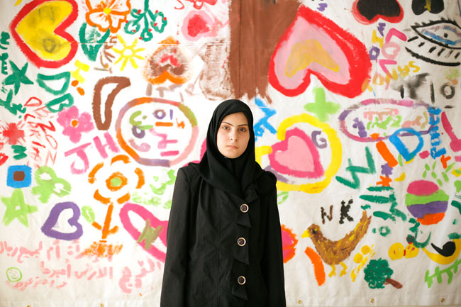 Amar, 18, a newly arrived Syrian refugee woman victim of a trauma, poses on June 19, 2014 at Caritas Migrant Center in Dahr El Ain, near Tripoli. Amar is catatonic and didn't speak for the last 6 months. The background shows a drawing made by 100 women for the Women's Day on March 8, 2014. Credit: Matthieu Alexandre/Caritas