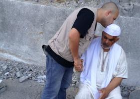 Caritas staff member Ameen Sabbagh comforting an injured man in Gaza. Credit. Caritas