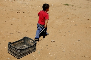 A Syrian boy plays with a plastic crate near a refugee camp in Lebanon.  Matthieu Alexandre for Caritas Internationalis.