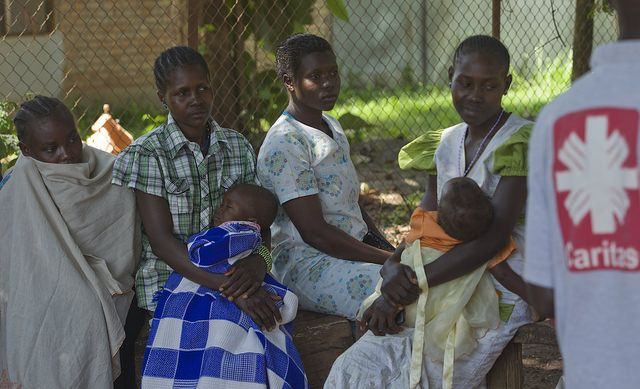 Mothers wait in line, as their young ones lay asleep in their arms, during an aid distribution in Yambio, South Sudan. Credit. Caritas