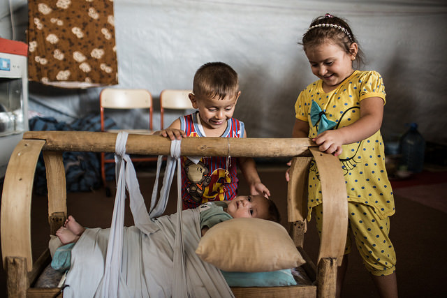 Children of an extended Christian family from the city of Bartyla, Iraq look out for a newborn in a construction site where they currently live, Ainkawa, Erbil, Iraq, Aug. 26, 2014. Photo by Daniel Etter for Catholic Relief Services