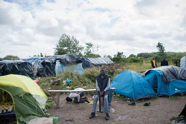 Refugees camp in Calais waiting to continue their journey into England.