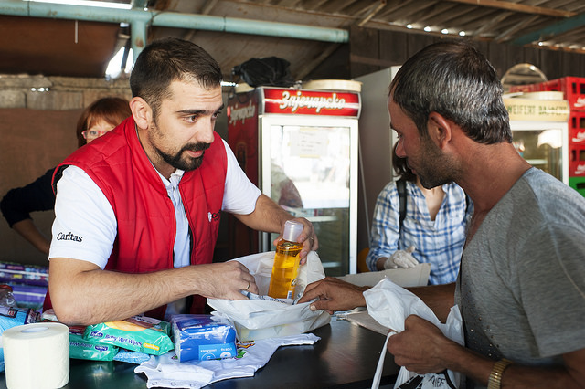 Dusan Peric with Caritas Valjevo passes out hygiene kits to refugees passing through Belgrade. Photos by Kira Horvath for Catholic Relief Services