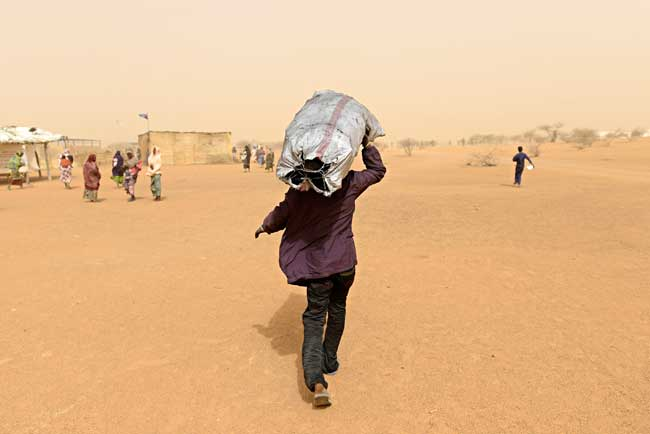 A Malian refugee takes charcoal to the tent where he's staying with his family. Photo by Simone Stefanelli/Caritas