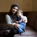 """Syrian refugee Reem, 30, and her daughter Ibtisan, 3, photographed at their home in Zarqa, Jordan. She has three children. Two of them attend public school and Caritas remedial classes. Previously they attended Caritas catch up classes after having missed one year of school.  """"I believe that the most important thing for my kids and for their future is education.""""   """"My hope is that they will have a better future and they won't have to live we have lived or see what we have seen. I never thought in my life I would live through something like this. """"  The classes her children attend are part of the project Education and Protection for Syrian Refugees in Jordan by Catholic Relief Services' partner Caritas Jordan. The project has a total of 7750 direct beneficiaries."""