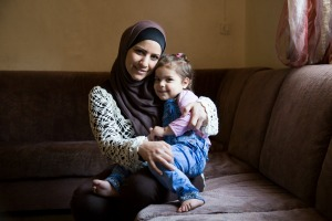 "Syrian refugee Reem, 30, and her daughter Ibtisan, 3, photographed at their home in Zarqa, Jordan. She has three children. Two of them attend public school and Caritas remedial classes. Previously they attended Caritas catch up classes after having missed one year of school.  ""I believe that the most important thing for my kids and for their future is education.""   ""My hope is that they will have a better future and they won't have to live we have lived or see what we have seen. I never thought in my life I would live through something like this. ""  The classes her children attend are part of the project Education and Protection for Syrian Refugees in Jordan by Catholic Relief Services' partner Caritas Jordan. The project has a total of 7750 direct beneficiaries."