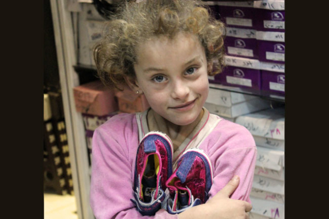 Fatimah,6, and her new shoes, bought with Caritas voucher.