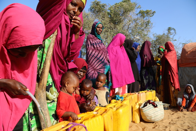 New arrivals at a camp on the outskirts of Mogadishu, Somalia, line up for water