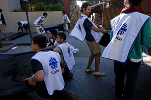 Caritas volunteers prepare tarps for distribution outside the Caritas headquarters in Talca, one of the major cities hit hard by the February 28th 8.8 magnitude earthquake in Chile.   Credit: Katie Orlinsky/Caritas 2010