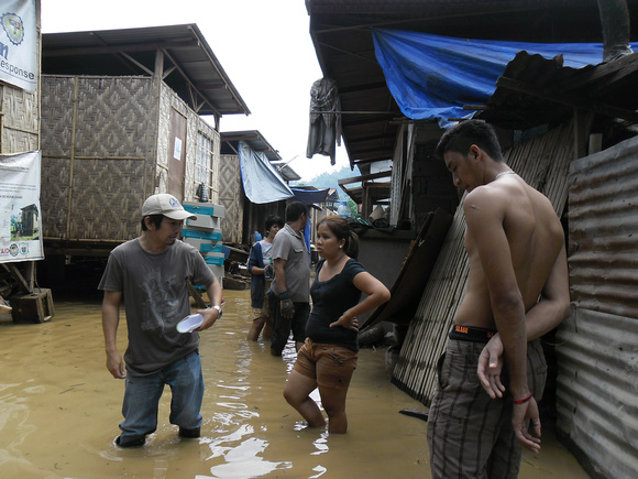 CRS (Caritas member in the USA) staffer Howard Bacayana stands in about a foot of water as he does a damage assessment in the city of Cagayan de Oro after Typhoon Bopha (known locally as Pablo) struck the Philippines on December 4, 2012. Credits: Salacion Pacatang/Catholic Relief Services
