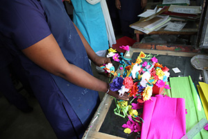 A young woman who survived sex trafficking in India shows paper flowers she made as part of a rehabilitation programme. Credits: Laura Sheahen/CRS