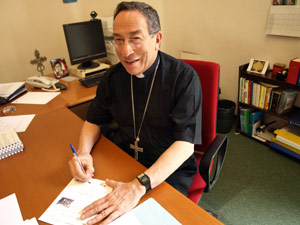 Cardinal Rodriguez signs the Caritas Japan postcard calling on their government to live up to promises on aid as hosts of this year's G8. Download postcard Credits: Caritas/Carofei