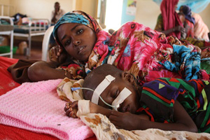 At a refugee camp in northeast Kenya, a mother and child lie in the malnutrition ward of a hospital. When children are too weak from hunger to eat, they are fed intravenously. Photo by Laura Sheahen/CRS Credits: Laura Sheahen/CRS