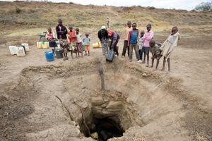 Locals in the village of Kalele in Kenya's Eastern Province gather what water they can from a hand dug well located at the site of a large scale dam project built in 2008 through Caritas Kenya. The dam, built through the Katangi Food Security Support Project, provided year round water to the local communities for two years. The withering drought the region now faces has dried the surface water of the 21,000 cubic meter pond. Credits: David Snyder/Caritas