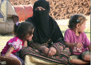Salwa with her two children in her tent. Many refugee families are facing the same issues. The working men have either gone back to Syria to fight, have been killed or as in Salwa's husband case, arrested. Credits: Caritas Lebanon