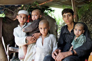 Sher Ali, 14 years old, is sitting with his brothers in a temporary shelter he made after his house washed away due to flood in Shangla district in Khyber Pakhtunkhwa province of Pakistan. Credits: Asad Zaidi/CRS