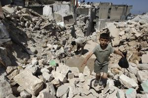 A boy walks on the rubble of buildings damaged by what activists said were missiles fired by Syrian Air Force fighter jets loyal to President Bashar al-Assad in Salqin city, Idlib governate, May 28, 2013. Credits: REUTERS/Muzaffar Salman
