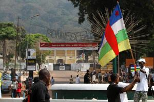 A man holds a Central African flag during a traders' demonstration near the presidential palace (seen in the background) in Bangui January 5, 2013. The U.N. Security Council voiced alarm on Friday at an advance by rebels in Central African Republic that has brought them within striking distance of the mineral-rich nation's capital, and renewed its call for a negotiated solution to the crisis. Credits: REUTERS/Luc Gnago courtesy of AlertNet.org