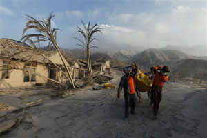Volunteers carry the body of a victim of the Mount Merapi eruption at Kinarrejo village in Sleman, near the ancient city of Yogyakarta, October 27, 2010. One of Indonesia's most dangerous volcanoes has killed at least 15 people since it began erupting, forcing thousands to flee mountain villages and blanketing nearby villages and towns in ash, witnesses said on Wednesday. Credits: REUTERS/Beawiharta