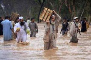 Residents and shopkeepers wade through a flooded street with their belongings after heavy rains in Peshawar July 29, 2010. Almost 200 people have been killed by flashfloods and bad weather in Pakistan in the last week, with the country's northwest and Baluchistan provinces bearing the worst of the storms, officials said on Thursday. Credits: REUTERS/FAYAZ AZIZ