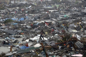 A man stands atop debris as residents salvage belongings from the ruins of their houses after Typhoon Haiyan battered Tacloban city in central Philippines. REUTERS/Erik De Castro courtesy Trust.org