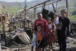Armoud Badion and his family in the remains of their house in Barayune in Palo diocese, which was destroyed by Typhoon Haiyan. Credit: Nick Harrop/CAFOD