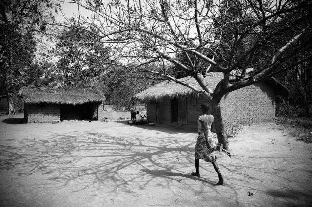 A woman walks to her home in Bossangoa. For months she had been hiding in the Cathedral. This short trip would have been too dangerous. Photo by Matthieu Alexandre for Caritas Internationalis
