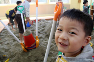 Children play in sandbox. Three years after the tsunami, 200,000 people are still living in temporary shelters. Credit: Caritas Japan