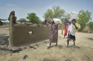 Mujeres desplazadas pasan por delante de casas incendiadas mientras vuelven a Bor, una ciudad del estado de Jonglei, de Sudán del Sur, que ha sido escenario de feroces combates en los últimos meses. Foto de Paul Jeffrey para Cáritas.
