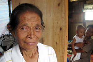 Violeta Ofianga lost almost everything she had to Typhoon Haiyan. She's living with her children and grandchildren – 10 people in all – in what remains of her house. Caritas gave them a tarpaulin to cover where their roof had been and keep the rain out. Credit: Nick Harrop/CAFOD