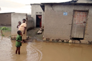 A woman and a child in front of a flooded house in Bujumbura. Credit: Caritas Burundi.