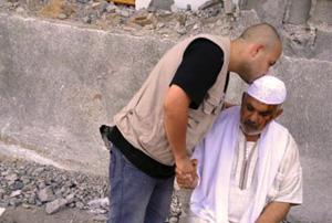 Ameen confortant Ismaël suite à la mort de membres de sa famille lors des bombardements sur Gaza. Crédit : Caritas Jérusalem
