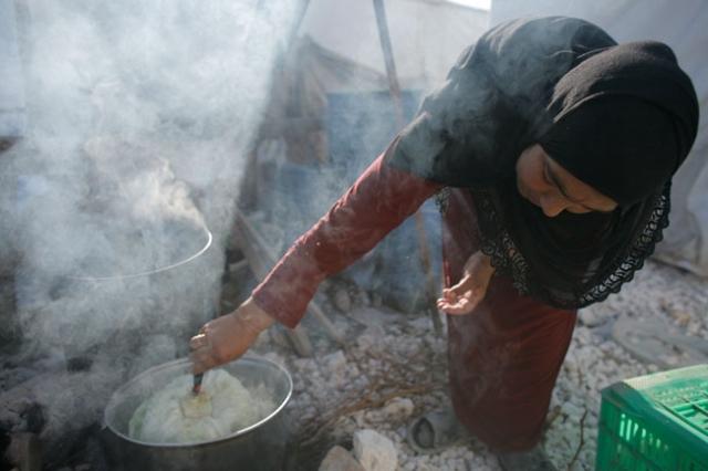 Une femme faisant la cuisine dans un camp de réfugiés syriens, le 18 juin 2014, dans le village libanais de Zahlé, dans la vallée de la Bekaa. Photo: Matthieu Alexandre/Caritas