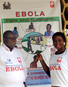 Fr. Peter with poster on signs and symptoms of Ebola. Photo by Caritas Sierra Leone